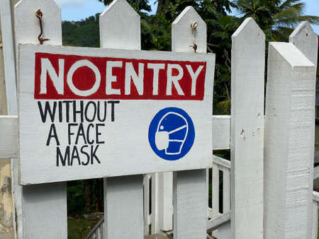 A No Entry Without Face Mask Sign on a fence.