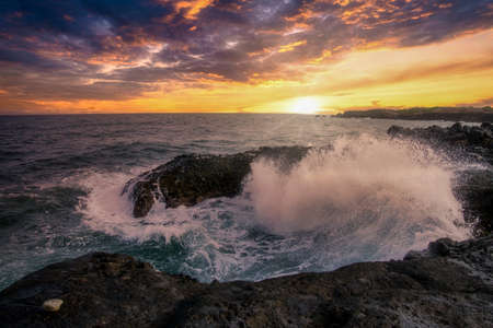 Waves crashing on the rocky shoreline of a small island witht he sunset colors in the sky.