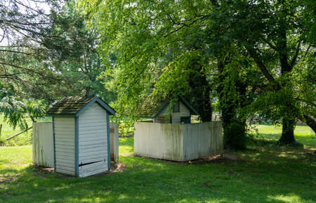 Two old outhouses under some big old trees at a school. 免版税图像