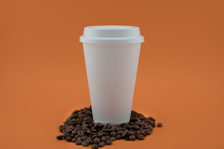 Paper coffee cup on coffee beans, orange background. The coffee cup is covered with the lid. Banque d'images