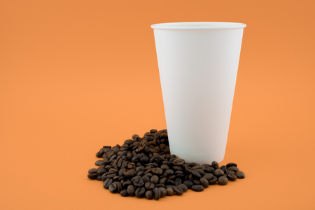 Take-out coffee cup on coffee beans, orange background. The coffee cup is open, without a lid.