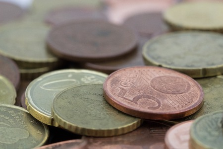 Euro cents coins with a small value. Savings of coins. Coins of fifty euro cents, twenty euro cents and five euro cents.