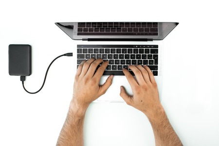 Overhead view of the hands of a person using his laptop on a white table. Business person working in his office. External hard drive connected to the computer. Modern workplace with laptop. Archivio Fotografico
