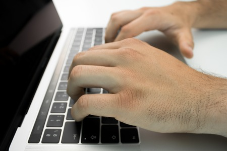 Hands using the keyboard and touchpad of a laptop computer on a white table. Modern workplace.