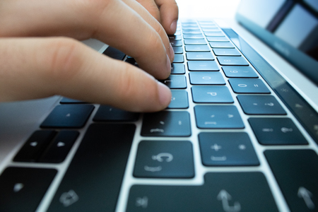 Manos usando el teclado y el panel táctil de una computadora portátil sobre una mesa blanca. Lugar de trabajo moderno.
