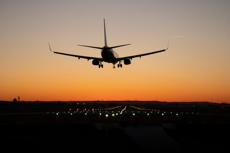 Commercial passenger airplane is landing on the airport runway during sunset. The sky is orange.