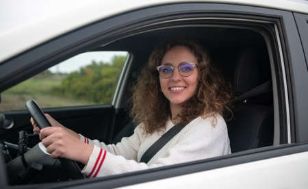Young woman smiling while holding the steering wheel of the car with her hands. The woman has curly blonde hair. New driver concept.