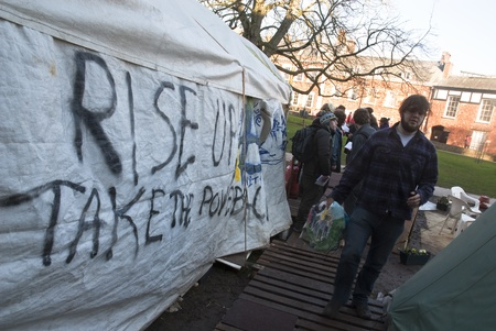 guy fawkes mask: Occupy Exeter activist Bench walks past a tent with Rise up and Take the Power painted on the side