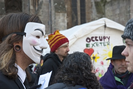 guy fawkes mask: An Occupy Exeter activist wearing a Guy Fawkes mask before the movements direct action against the Exeter branches of Topshop, HSBC and Vodaphone. Editorial