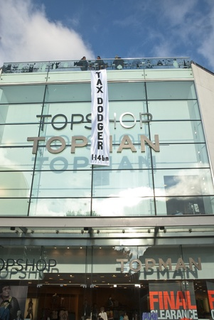 guy fawkes: The Occupy Exeter banner saying Tax Dodger 1.4bn hangs down the front of the Exeter Branch of Topshop.