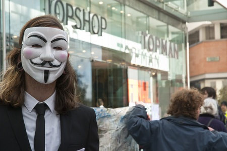 An Occupy Exeter activist wearing a Guy Fawkes mask outside the Exeter branche of Topshop
