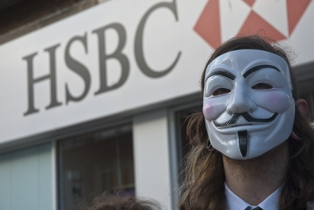 guy fawkes mask: Occupy Exeter activist wearing a Guy Fawkes mask campaigning outside the Exeter branch of HSBC bank