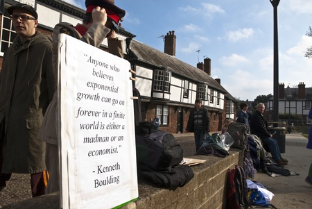 occ: Stuart Crewes, aka Genral Assembly prepares his uniform behind a sign with a quote by Kenneth Boulding.  Members of the public watch on during Occupy Exeter leaving celebration on Exeter Cathedral Green. Editorial