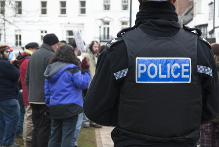 A Devon & Corwall policeman watches the Occupy Exeter activists as they celebrate their achievments during their leaving the green event in Exeter
