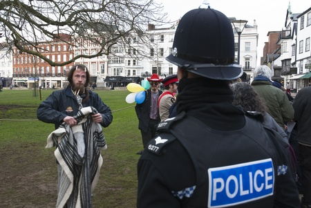 A Devon & Corwall policeman has a discussion with Occupy Exeter activist over the dropping of a clothes peg  during Occupy Exeters leaving the green event in Exeter