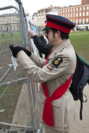 occ: Stuart Crewes, aka Genral Assembly ties a message card to the temporary fencing surrouding the former Occupy Exeter camp, during Occupy Exeter leaving celebration on Exeter Cathedral Green.