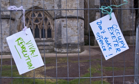 Two cards reading  Viva Revolution and Occupy Exeter, Dont take a fence! tied to the temporary fencing surrounding the former Occupy Exeter camp on Exeter cathedral Green.