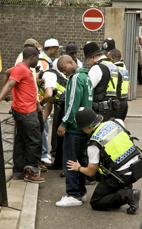 Police officers searching young black people during the Notting Hill Carnival in London