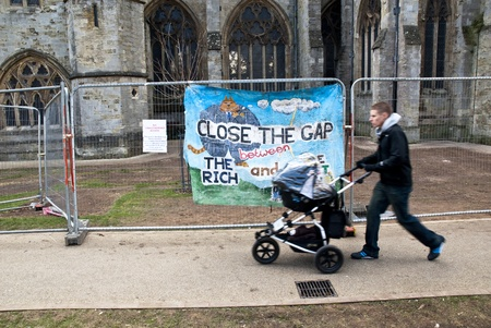 occ: A man with a baby buggy walks past a banner saying Close the Gap on the Rich tied to the  temporary fencing surrounding the area that was used by Exeter Occupy activists to have their camp.