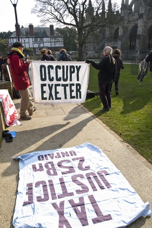 ows: Occupy Exeter activist hold up an Occupy Exeter banner on Exeter Cathedral green during the Occupy Exeter leaving the Exeter Cathedral Green event in Exeter. Editorial