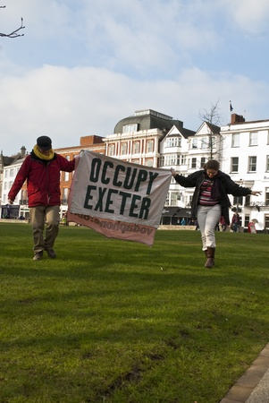 occ: Occupy Exeter activist hold up an Occupy Exeter banner on Exeter Cathedral green during the Occupy Exeter leaving the Exeter Cathedral Green event in Exeter. Editorial