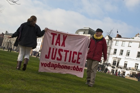 occ: Occupy Exeter activist hold up a Tax Justice banner on Exeter Cathedral green during the Occupy Exeter leaving the Exeter Cathedral Green event in Exeter.