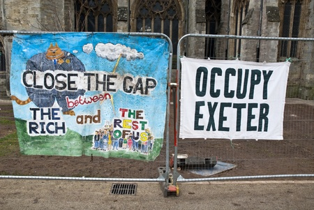 occ: A banner saying Close the Gap on the Rich and a Occupy Exeter banner tied to the  temporary fencing surrounding the area that was used by Exeter Occupy activists to have their camp.