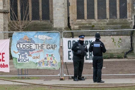 occ: Policemen standing by banner saying Close the Gap on the Rich and a Occupy Exeter banner tied to the  temporary fencing surrounding the area that was used by Exeter Occupy activists to have their camp.