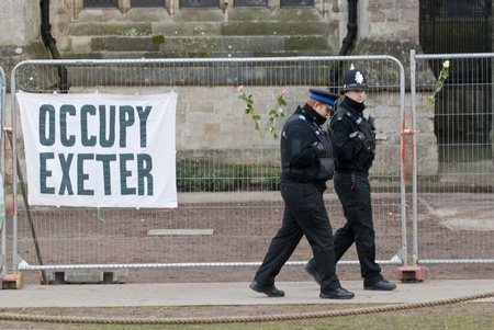 occ: Policemen walk past an Occupy Exeter banner tied to the  temporary fencing surrounding the area that was used by Exeter Occupy activists to have their camp.