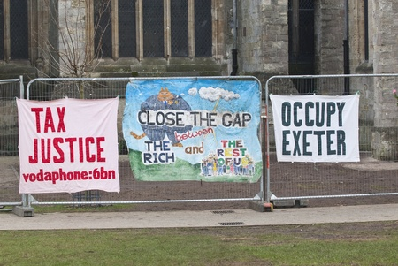 occ: A Tax Justice banner, another banner saying Close the Gap on the Rich and a Occupy Exeter banner tied to the  temporary fencing surrounding the area that was used by Exeter Occupy activists to have their camp.