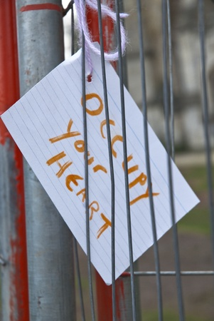 occ: A card reading  Occupy Your Heart tied to the temporary fencing surrounding the former Occupy Exeter camp on Exeter cathedral Green. Editorial