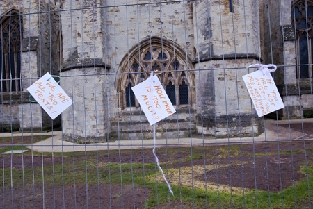 occ: Three cards reading  We are all two Tents,  How Much is to Much and If you are not angry, you are not paying attention tied to the temporary fencing surrounding the former Occupy Exeter camp on Exeter cathedral Green. Editorial