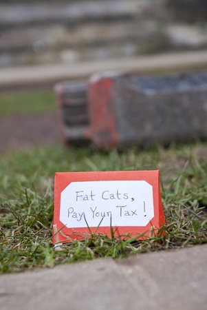 occ: A little cardboard tent that says Fat Cats Pay Your Tax set up on the former Occupy Exeter campsite on Exeter Cathedral Green.