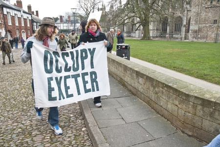 ows: Occupy Exeter activist march out of the Cathedral grounds during the Occupy Exeter leaving the Exeter Cathedral Green event in Exeter.