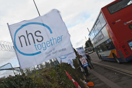 nhs: An NHS Together flag flaps in the wind as a bus travels past, on Barrack Road in Exeter, during the NHS reform protest outside the Royal Devon & Exeter Hospital.