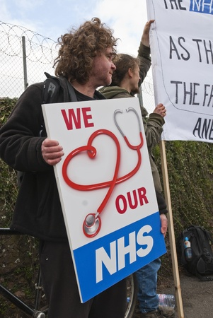 outcry: Activist Bruce Chapman holds a placard that says We Love our NHS, during the NHS reform protest outside the Royal Devon & Exeter Hospital.