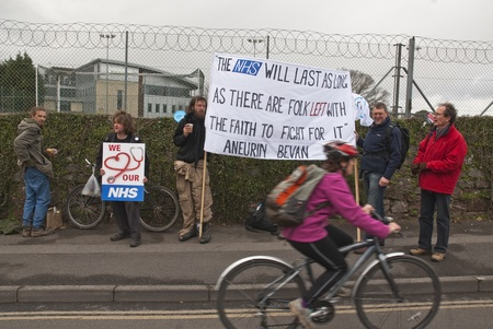 nhs: A cyclist travels past a sign that has a quote from Aneurin Bevan, who spearheaded the establishment NHS, during the NHS reform protest outside the Royal Devon & Exeter Hospital.