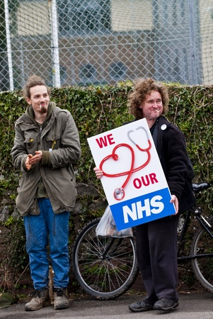 nhs: Activist Bruce Chapman holds a placard that says We Love our NHS, during the NHS reform protest outside the Royal Devon & Exeter Hospital.