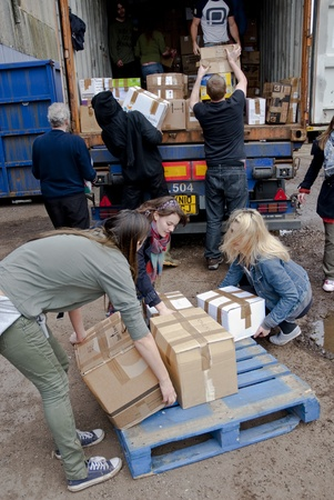 loads: Volunteer from BookCycle loads a box into the container that is taking donated book to Ghana