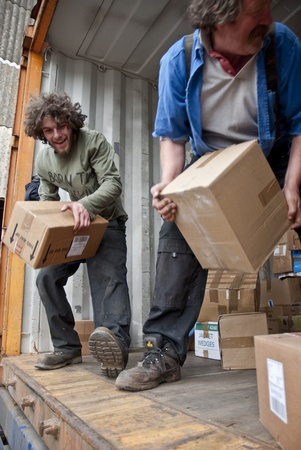 Volunteers from BookCycle stack boxes inside the container that is taking donated books to Ghana Stock Photo - 12573062