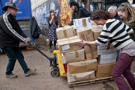 work load: Volunteer from BookCycle move a pallet of boxed books to the container that is taking donated book to Ghana