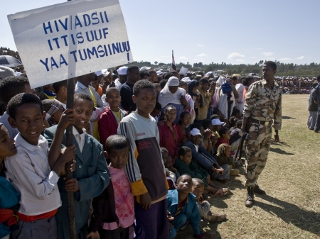 Children holding an HIV banner, with an Ethiopian Soldier with a gun behind them at the 20th World Aids Day event in Fitche, Ethiopia