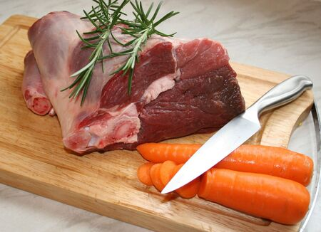 A joint of lamb ready for cooking,with carrots and rosemary photo