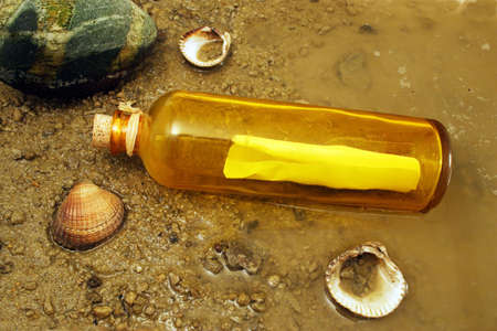 A message in a bottle washed up on the shore Stock Photo