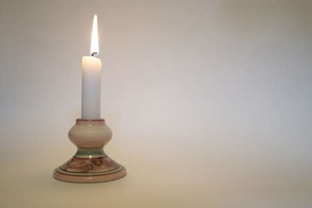 A simple candle lit with space for a message