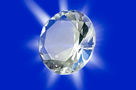 A photo of a diamond on a blue background with starburst Stock Photo