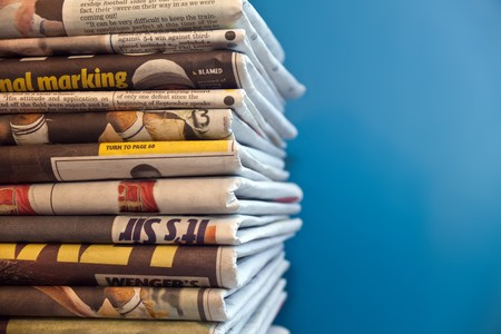 A stack of newspapers with a blue background Stock Photo