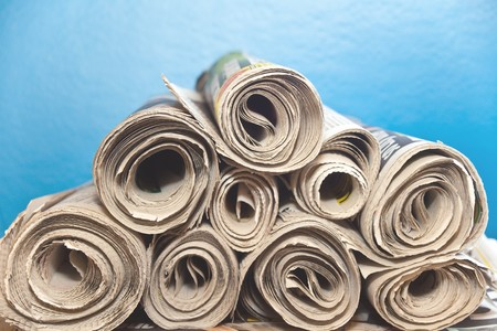 A stack of old rolled up newspapers with a blue background