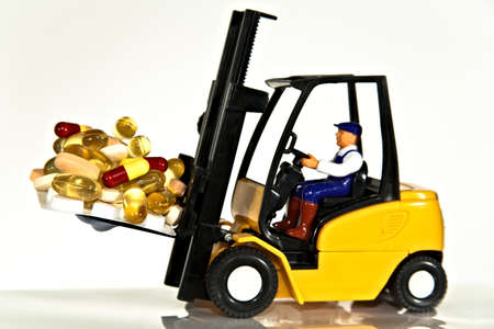 A toy fork lift truck lifting a pallet full of drugs or tablets
