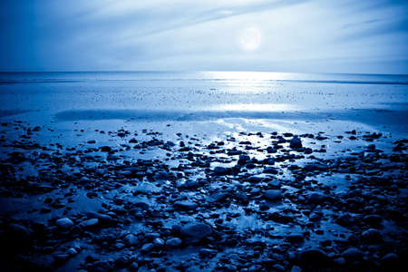 The rising moon reflected in the ocean from a beautiful bay photo